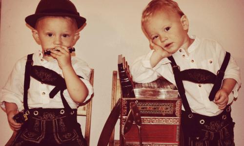 Auf diesem Bild befinden sich zwei Kinder in bayerischer Tracht mit Mundharmonika und steirischer Harmonika
